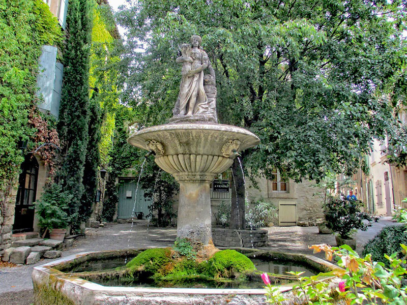 Stone fountain with a statue of a woman, in a small flower filled square in France