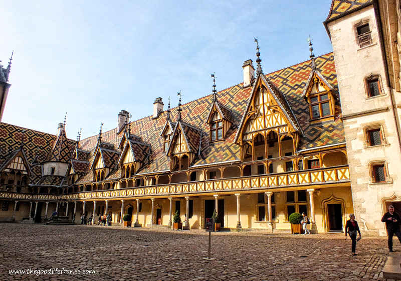 Ancient hospital in Beaune, Burgundy with colourful tiled roof and pointed gable architecture and towers