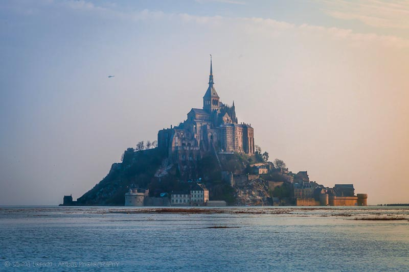 Island village of Mont Saint-Michel in Normandy, topped by an Abbey with a pointed spire