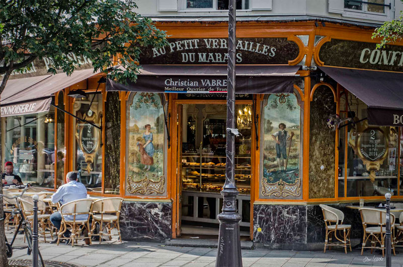 Beautiful boulangerie in Paris with tiled front, people seated at tables in front enjoying coffee and croissants