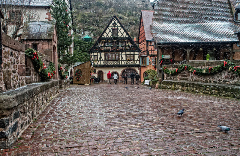 Pretty cobbled street festooned with holly as snow falls at Christmas in Kaysersberg