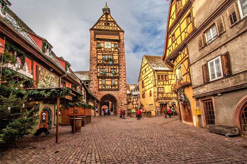 Cobbled street lined with colourful half-timbered houses, Riquewihr, Alsace