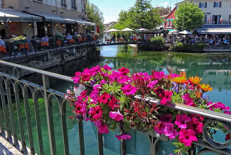 View from a bridge across a lake lined with restaurants and diners eating al fresco, Isle-sur-la-Sorgue France