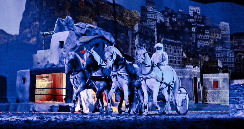 Night time snow at the Puy du Fou theme park in France, horse and carriage lit up