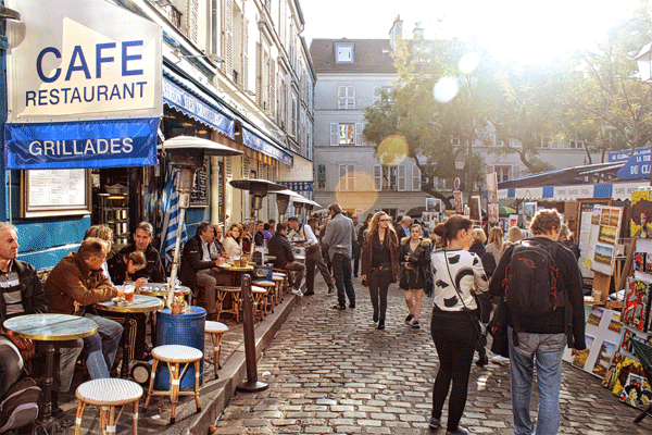 Lots of people sitting at tables outside a Paris cafe and people walking in a cobbled street on a sunny day