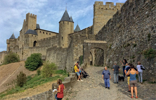 Arched stone gate to the ancient city of Carcassonne on top of a hil;