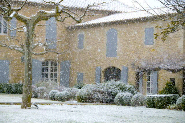 Snow falling in Provence, a pretty house with shutters in the background
