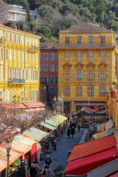 The market place of Nice, southern France, bright sunlight, colourful buildings and market awnings