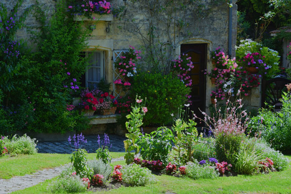 Facade of a house in blaye with flowers in pots, climbing up the walls and the garden