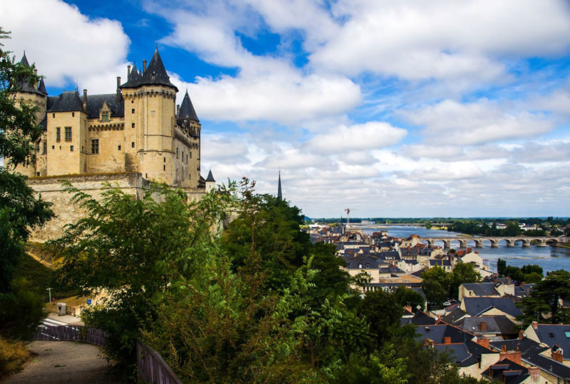 Castle overlooking a river crossed by an arched stone bridge, ancient houses line its banks, Saumur, Loire Valley