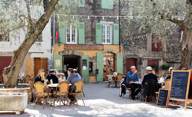 A small square lined with buildings which have shutters, people enjoying drinks at tables