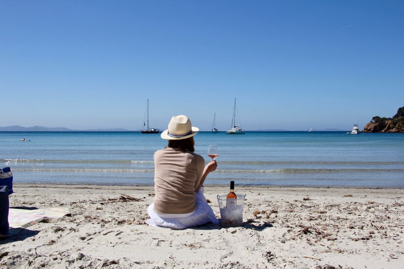 Woman sits on a beach, her back to the camera, holding a glass of wine looking at the blue sea on a sunny day