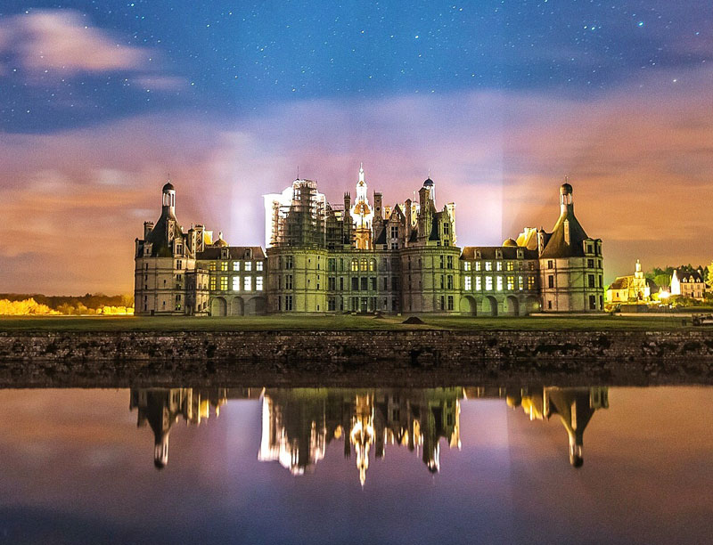 Chateau with turrets and towers under a starry night sky, a pink haze surrounds it