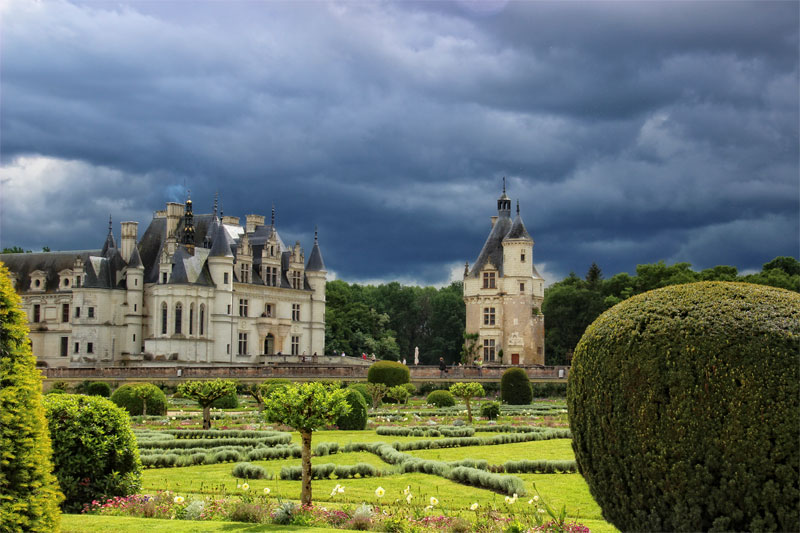 The Chateau of Chenonceau surrounded by formal style gardens, planted beds under a stormy sky