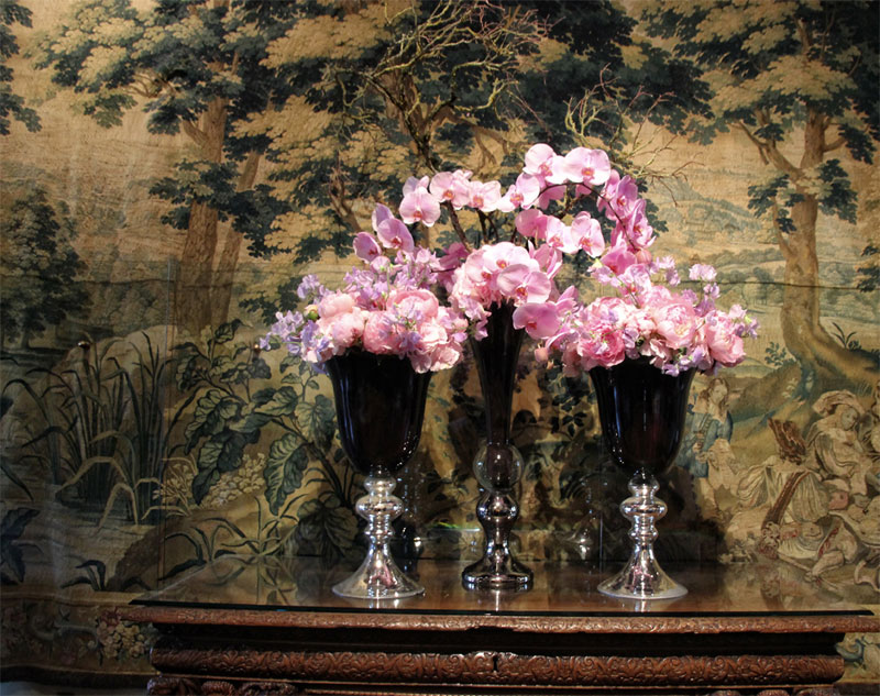 Flowers displayed in antique goblets on a sideboard at the Chateau de Chenonceau