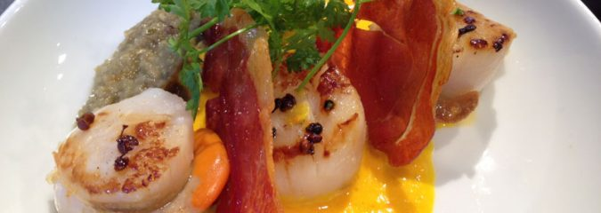 Roasted scallops with parma ham, leeks and mango sauce