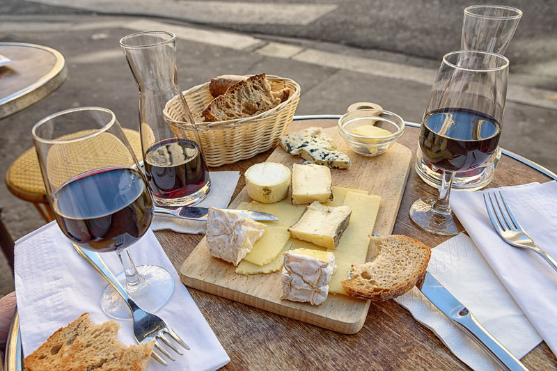 Cheeses on a wooden board and a carafe and glasses of red wine