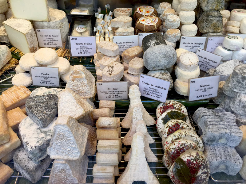 Market stall in France piled with cheeses of all sorts