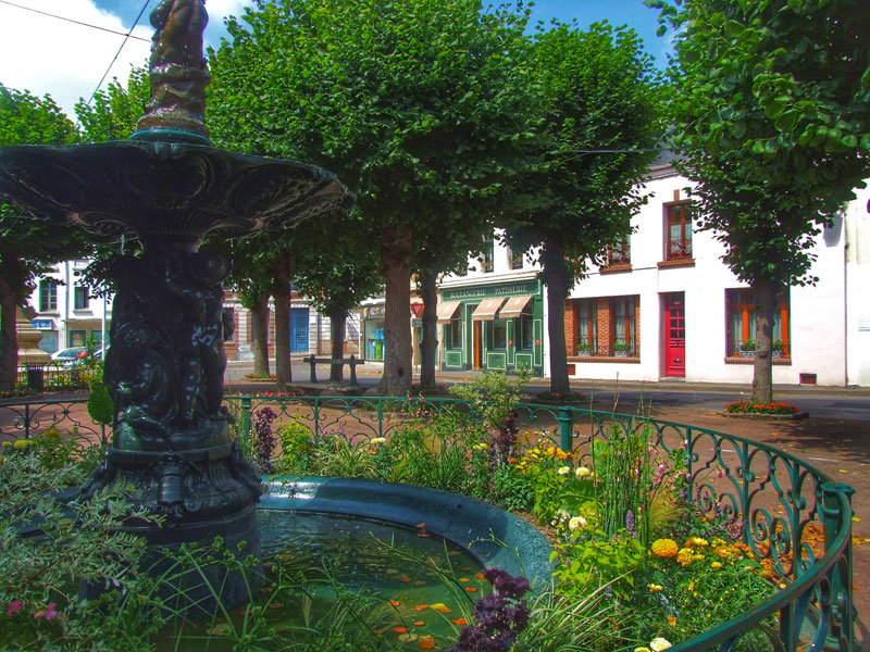 Pretty fountain in a town square in Montreuil-sur-Mer, surrounded by plants and trees