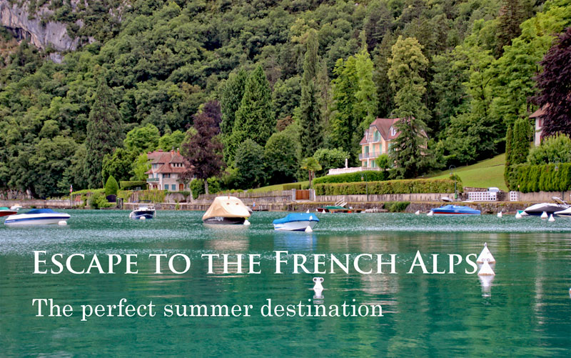 Bay of Lake Annecy, tiny boats bob on the crystal clear water and the cliffs and hills are covered in lush foliage