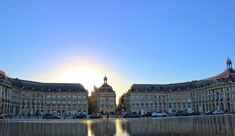 Water sculpture reflecting sunlight in Bordeaux, surrounded by elegant bulidings