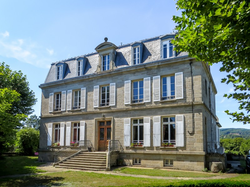 Small 3-storey chateau with white shutters and grand steps leading to front door