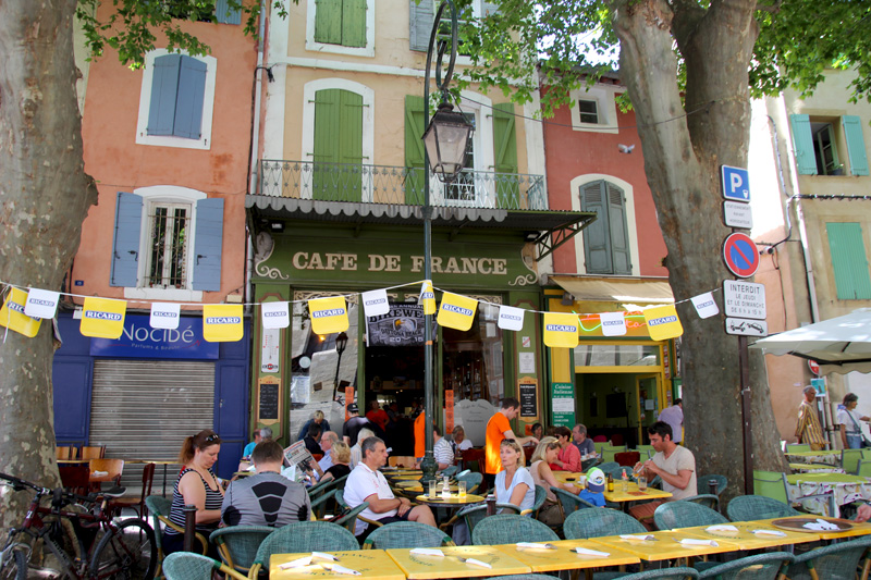 People sitting outside a cafe in France, plane trees give shade