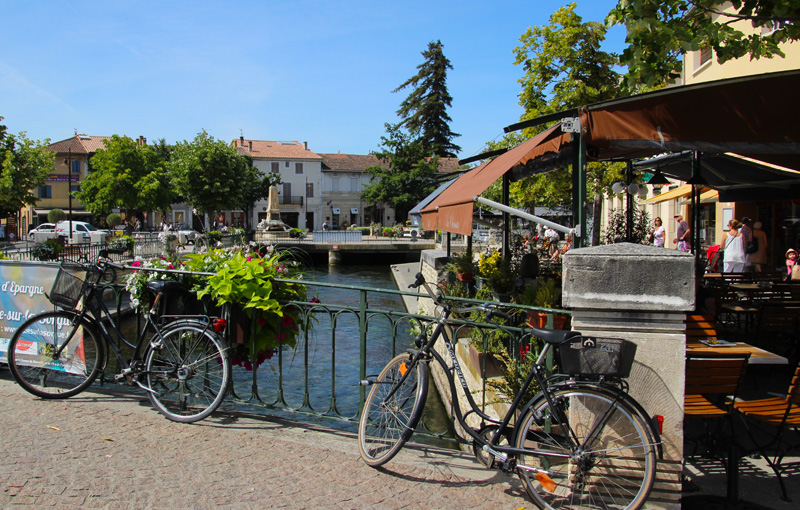 Bikes leaning against a wrought iron bridge over a river running through Isle-sur-la-Sorgue Provence