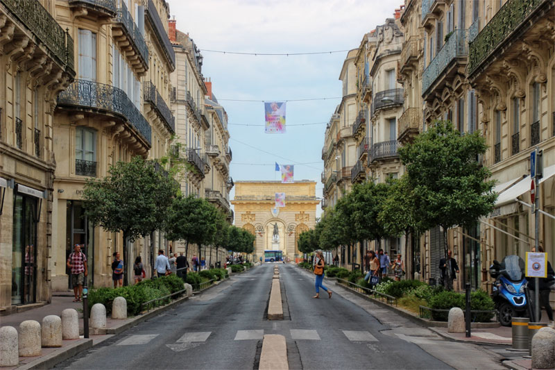 A Roman looking arch at the end of a street, lined with smart, Parisian style buildings in Montpellier