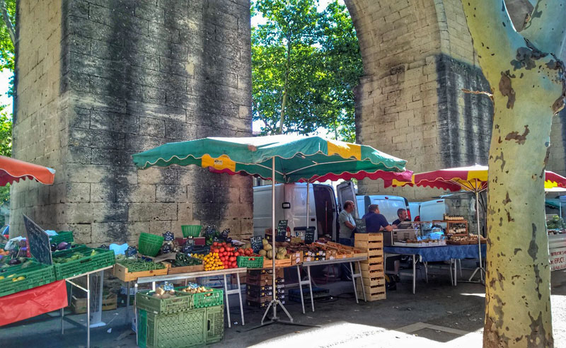 Market stalls against the walls of a tall aqueduct, plane trees cast shade over their colourful awnings