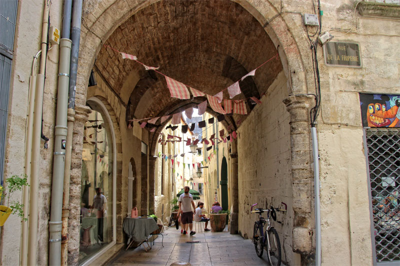 Paved street with colourful flags hanging across it in Montpellier, southern France