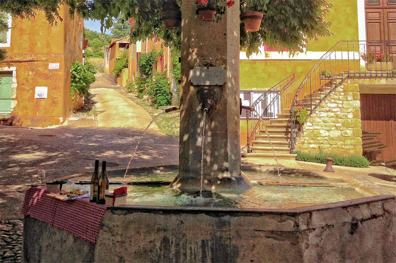 Fountain spewing water into a round stone trough, bottle of wine and glasses on the side