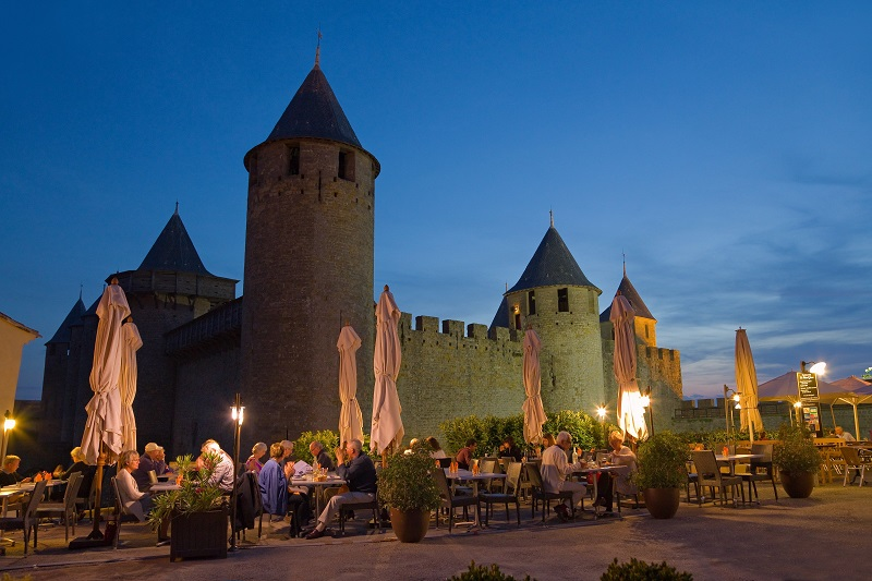 People dining outside in the shadow of an ancient castle with atmospheric lighting