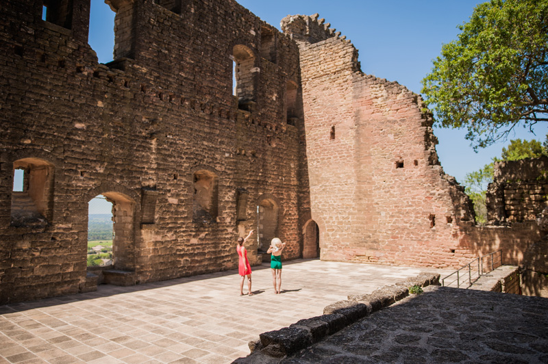 Two women stand in the ruins of a castle under a blue sky, the sun pours down
