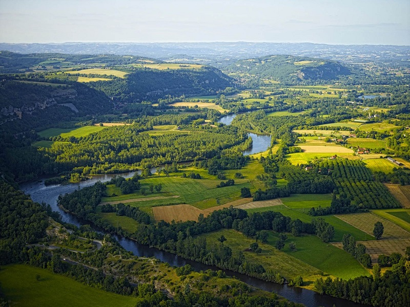 Aerial view of Dordogne, covered in forests and fields with the River Dordogne running through