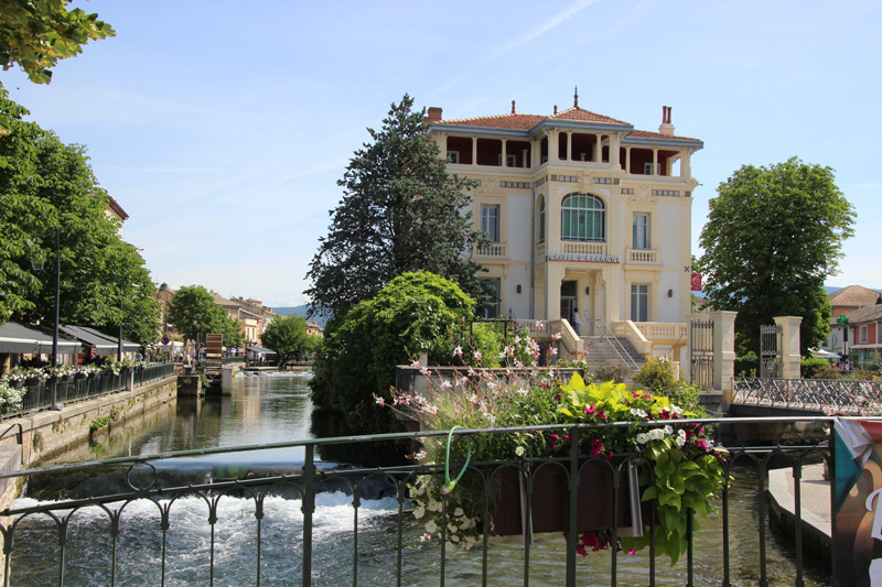 Provencal style house on an island in a river under a blue sky