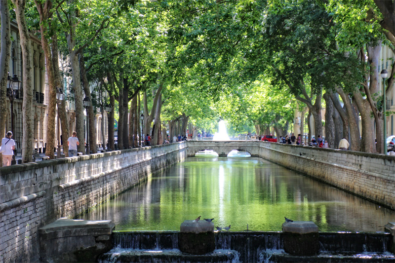 Beautiful river running through Nimes, trees either side cast shade