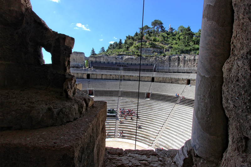View from the top of the walled Roman theatre of Orange looking over tiered stone benches, Provence France