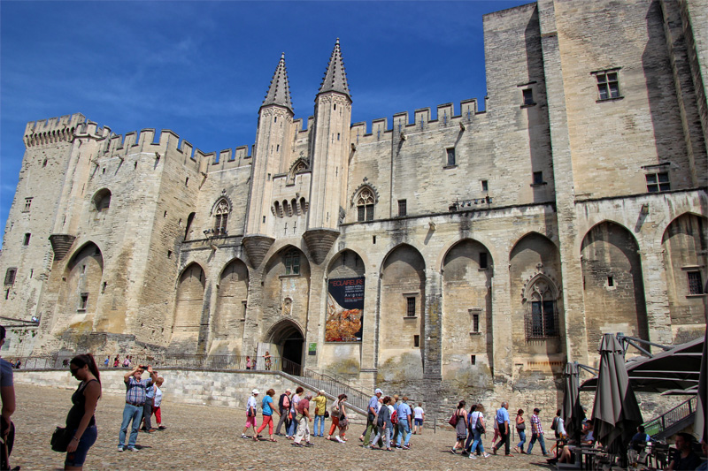 Monumental castle, the pale stone walls of Palace of the Popes in Avignon now a major tourist attraction