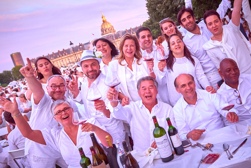 Attendees at Diner en Blanc Paris 2018 hold their glasses up and say cheers to a great night out