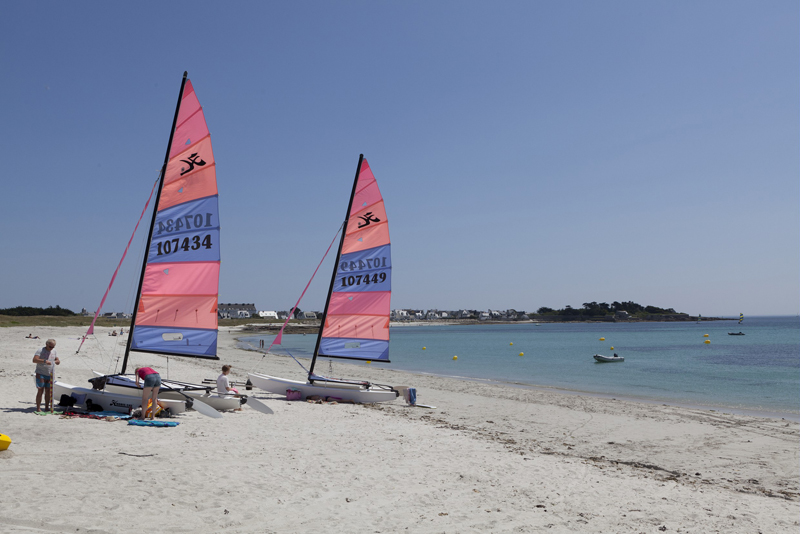 Small boats with tall sails parked on a white sandy beach under a blue sky in Brittany