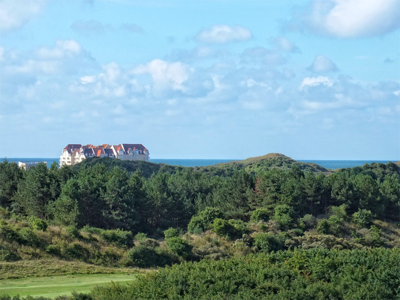 View from a golf course surrounded by trees next to the sea at Le Touquet