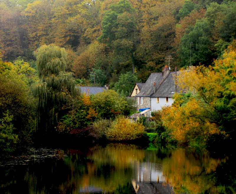 Peaceful river lined with pretty cottages and autumnal trees in Mayenne, France