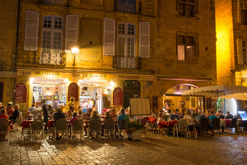 People dining out at night time at an old brasserie in Sarlat, Dordogne