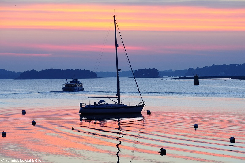 A sail boat in a tranquil bay under a sky layered pink and purple at sunset