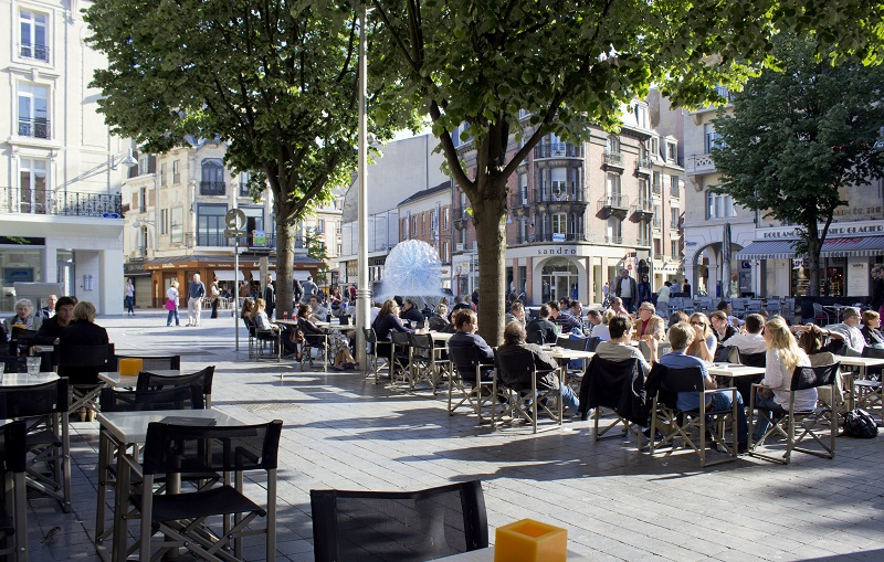 Tree lined square in Reims, Champagne people sit in the sun drinking Champagne