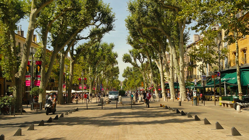 The main avenue of Aix-en-Provence, Cours Mirabeau, lined with plane trees and colourful shops and restaurants