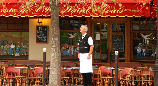Waiter stands outside an empty cafe in Paris, autumn leaves drop from a tree near by