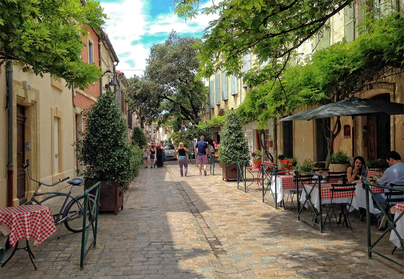 Tree-lined, cobbled street with tables and chairs outside a cafe in Aigues-Mortes, a town in southern France