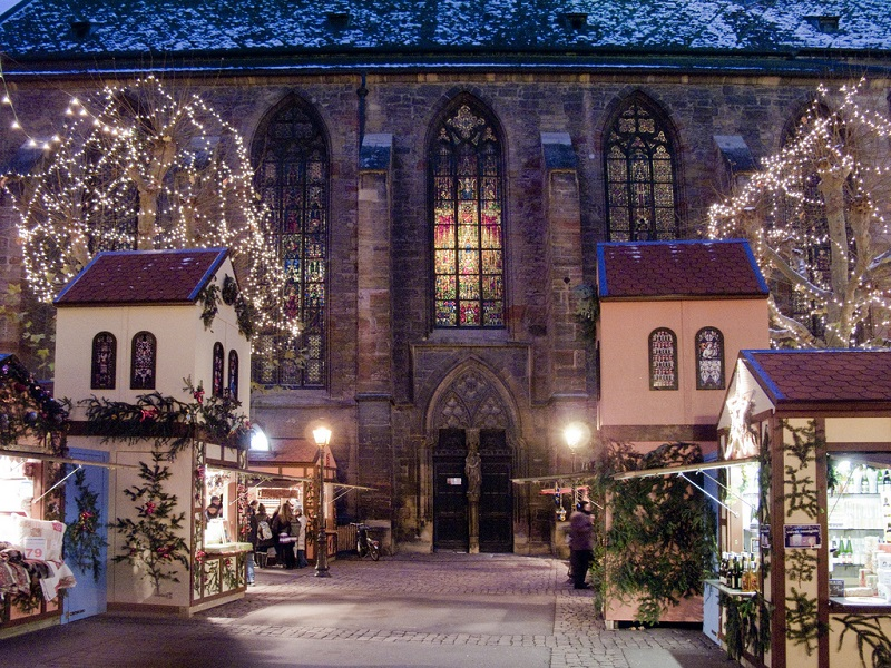 Cathedral of Colmar lit up at night with Christmas style chalets in France and twinkling tree lights